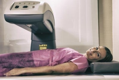 Woman in her 40s undergoing scan at bone densitometer machine.